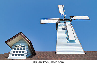 wind turbines and window on roof with blue sky background