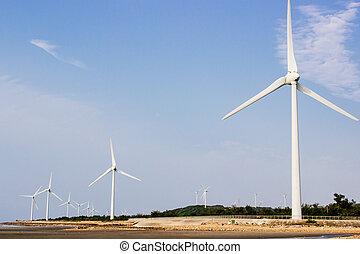 Wind turbines at seaside against blue sky