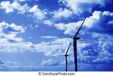 Wind turbines blue tint - Two wind turbines against fluffy ...