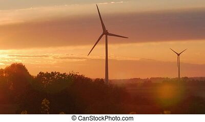 Wind turbines farms with rays of light at sunset in the...