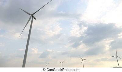 Wind turbines generating electricity with sky sun and clouds background.