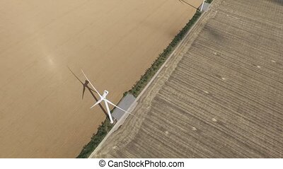 Wind turbines generating lot energy in golden fields. Aerial...