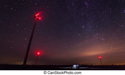 Wind turbines generating power at night timelapse with rotating starry sky on a background