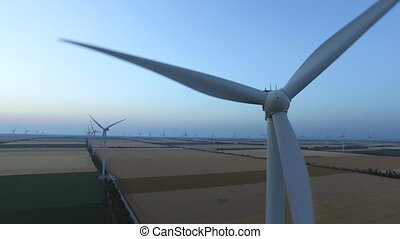 Wind turbines in fields near the sea driven with the sea breeze. Aerial survey. Close up
