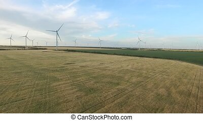 Wind turbines in wheat fields in the summer. Aerial survey
