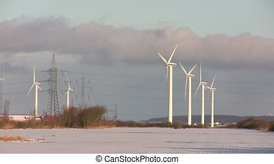 Wind turbines and snow filled field in the foreground. The sun is low and leaves a warm afternoon light.