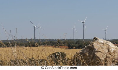 Wind Turbines on a Background of Stone in the Desert of...