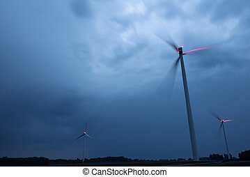 Wind turbines on a dramatic dark blue clouds in the sky. Storm ahead is coming. Red warning light on the windmill.