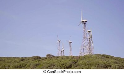 Wind turbines on a hilltop against a sunny blue sky...