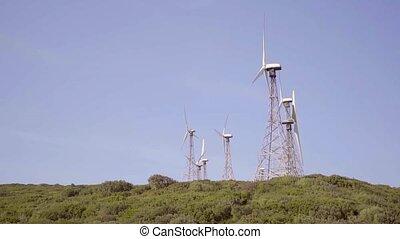 Wind turbines on a hilltop against a sunny blue sky...
