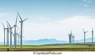 Wind turbines on green field over blue sky.