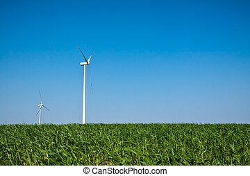 Wind Turbines on green field with blue sky