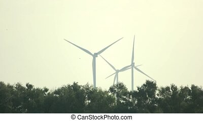 Wind turbines on sky background.