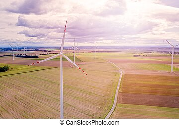 Wind turbines on the field during cloudy day