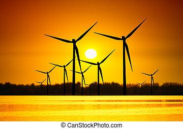 Wind turbines over sunset