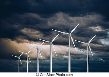 Wind turbines power generators on a stormy dramatic sky Eolic energy concept Renewable and sustainable energy