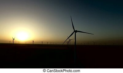 Wind turbines regenerative source of energy in the warm glow of sunset. Silhouette. Aerial survey