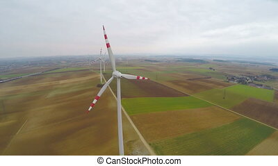 """Wind turbines rotating on green field. Alternative source of energy. Aerial view"""