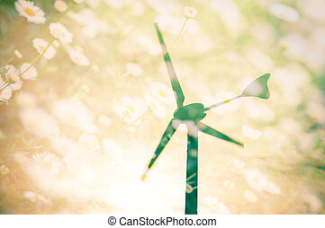 Wind turbines silhouette at sunset with flower field background