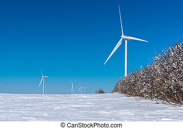 Wind turbines tower above a row of trees covered in horror frost in a Saskatchewan winter