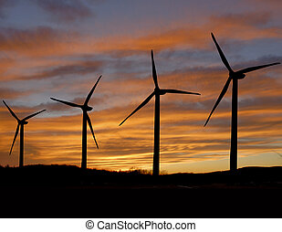 Wind turbines - Wind turbine propellers back lit by sunset