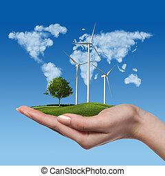 Wind turbines with tree in female hand - Wind turbines on...