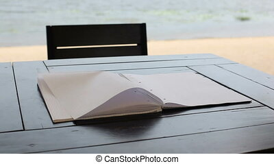 Wind turns the pages of a blank notepad lying on the table....
