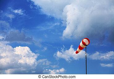 Wind vane - A red wind vane against a blue cloudy sky
