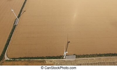 Wind vane green energy against the yellow plains. Aerial...