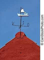 Wind vane sailing vessel at a cottage on the beach in...