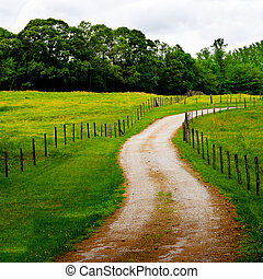 Winding country road with barbed wire fence