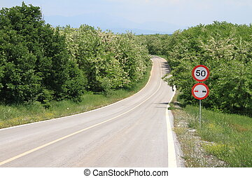 Winding country road with speed limit sign
