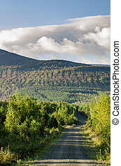 Winding dirt road hills clouds morning
