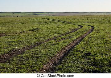 Winding dirt track through farm fields