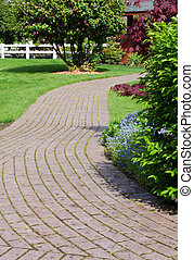 Winding garden path with white fence