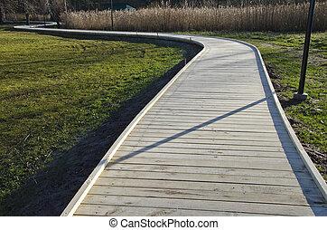 winding new wooden path walkway in park