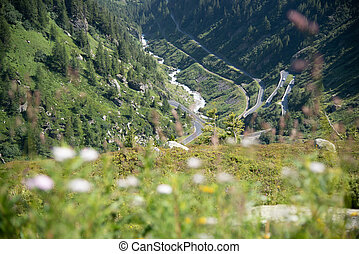 winding pass road in the Swiss Alps surrounded by mountains
