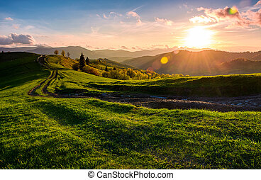winding road along the grassy rural hill at sunset. gorgeous...