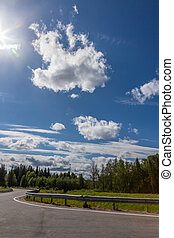 Winding road in the forest under the blue sky with clouds, Karelia. Russia