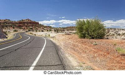 Winding road wih cars through empty