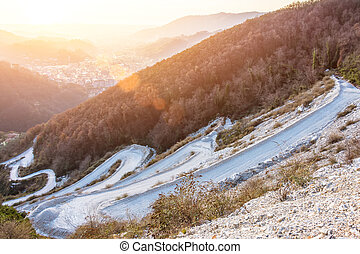 Winding serpentine road among rising to the rocky mountains. During sunset lights.