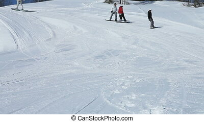 Winding snowboard ride - Four snowboarders taking a slow...
