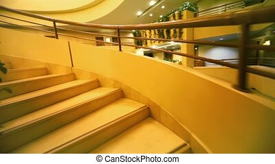 Winding staircase in multiple floor hotel, upward motion