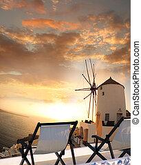 Windmill against colorful sunset, Santorini, Greece -...