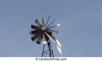 windmill air pump turning against a blue sky