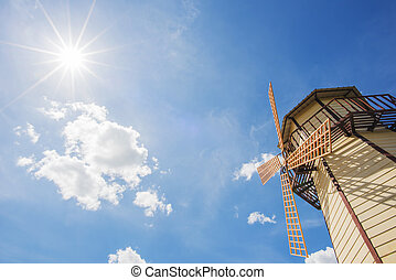 windmill and blue sky with sun star