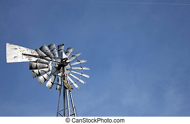 Windmill blades and bright blue sky