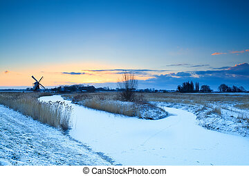 windmill by frozen river at sunrise, Groningen