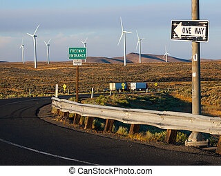 Windmill Farm on a Mountain with One Way Signs Pointing to a Freeway at Dusk