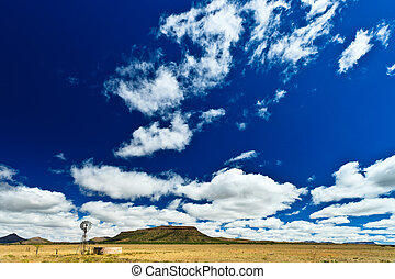 Windmill in a desolate landscape with beautiful cloudscape